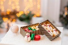 Varietà di maccheroni dolci in contenitore di cartone Biscotto sotto forma di pupazzo di neve Carta di Buon Natale Umore di nuovo immagini stock libere da diritti
