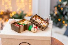 Varietà di maccheroni dolci in contenitore di cartone Biscotto sotto forma di pupazzo di neve Carta di Buon Natale Umore di nuovo fotografia stock