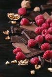 Varietà di spezzettamento del cioccolato a pezzi con i lamponi Fotografia Stock