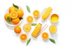Varietà di succo d'arancia in bottiglie e vetri, paglie, arance isolate sulla vista superiore del fondo bianco Immagine Stock