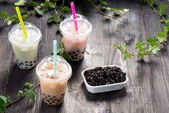 Varietà di tè della bolla in tazze di plastica con le paglie sull'tum di legno immagini stock
