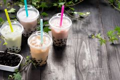 Varietà di tè della bolla in tazze di plastica con le paglie sull'tum di legno fotografia stock libera da diritti