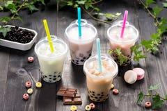 Varietà di tè della bolla in tazze di plastica con le paglie sull'tum di legno immagine stock libera da diritti