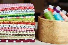 Varietà di tessuti di cotone e di scatola di legno con il filo Immagine Stock