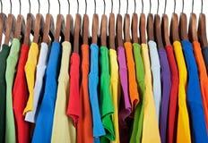 Varietà di vestiti multicolori sui ganci di legno Fotografia Stock Libera da Diritti