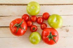 Varietà differenti di pomodori su un fondo di legno immagini stock libere da diritti