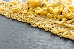 Varietà di tipi e di forme di paste italiane su un BAC scuro della pietra Immagine Stock
