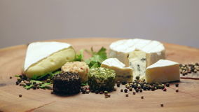 Varieties of cheese with herbs and peppercorns on a wooden board, rotating stock video footage