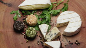 Varieties of cheese with herbs and peppercorns on a wooden board, rotating stock video