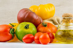 Varieties of colorful tomatos and olive oil Stock Photos