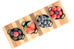 Varieties of fresh berries in individual dishes royalty free stock photo