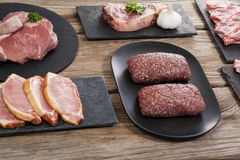 Varieties of meat on black tray. Against wooden background Stock Photos