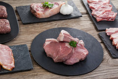 Varieties of meat on black tray. Against wooden background Stock Photography