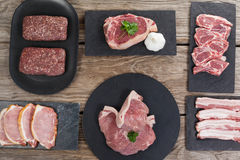Varieties of meat on black tray. Against wooden background Royalty Free Stock Photography