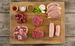 Varieties of meat and spices on wooden tray. Against wooden background Stock Image