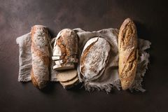 Variety of Artisan bread. Variety of loafs fresh baked artisan rye and whole grain bread on linen cloth over dark brown texture background. Top view, copy space royalty free stock image