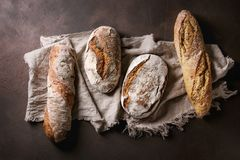 Variety of Artisan bread. Variety of loafs fresh baked artisan rye and whole grain bread on linen cloth over dark brown texture background. Top view, copy space Stock Photos