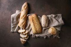 Variety of Artisan bread. Variety of loafs fresh baked artisan white and whole grain bread on linen cloth over dark brown texture background. Top view, copy stock image