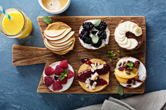 Variety of bagels on a board. Variety of bagels with different toppings for breakfast on a board Royalty Free Stock Photos