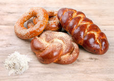 Variety of baked buns on wood table. Bagels, braided bread and flour on a wooden table stock image