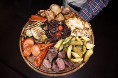 A variety of baked meat, fish, vegetables on a wooden board stock photo