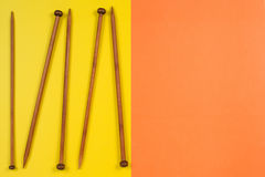 Variety of bamboo knitting needles in different sizes on yellow and orange background Royalty Free Stock Photo