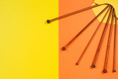 Variety of bamboo knitting needles in envelope on yellow and orange background Royalty Free Stock Image