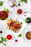 Variety of Belgian wafers with berries, chocolate and syrup Royalty Free Stock Photos