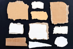 Variety of blank torn paper and cardboard. On black background royalty free stock photo