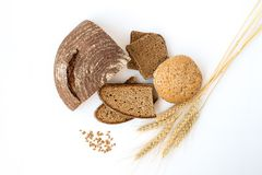 Variety of bread and stalks of wheat. Isolated on white Royalty Free Stock Images