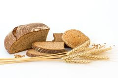 Variety of bread and stalks of wheat. On white Stock Photos