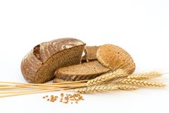 Variety of bread and stalks of wheat. On white royalty free stock photo