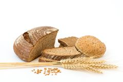 Variety of bread on white. Variety of bread and stalks of wheat on white stock images