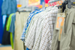 Variety of bright shirts and trousers on stands Royalty Free Stock Images