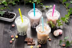 Variety of bubble tea in plastic cups with straws on a wooden ta royalty free stock image