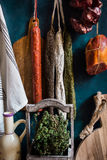 Variety of charcuterie sausages hanging on twine on hooks, wood cutting bard, herbs, linen towel, kitchenware. Pantry style, rustic Royalty Free Stock Images