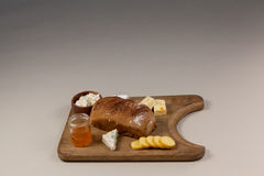 Variety of cheese with bread and sauce on chopping board Royalty Free Stock Photo