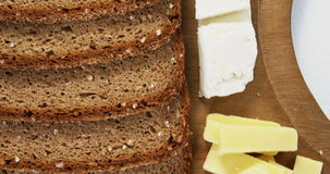 Variety of cheese with brown bread on wooden board. Close-up of variety of cheese with brown bread on wooden stock video footage