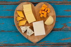 Variety of cheese on heart shaped chopping board. Close-up of various cheese on heart shaped chopping board royalty free stock images