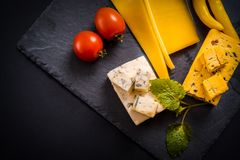 Variety of cheese, olives, prosciutto, over grey marble background, selective focus, square crop. Yellow hot pepper, cherry tomato Royalty Free Stock Photography