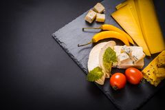 Variety of cheese, olives, prosciutto, over grey marble background, selective focus, square crop. Yellow hot pepper, cherry tomato Stock Images