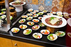 A variety of cheese varieties and meat delicacies with salads and other fresh sliced. A variety of cheese varieties and meat delicacies next to the table with royalty free stock image