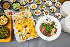 A variety of cheese varieties and meat delicacies. Next to the table with salads and other fresh sliced stock images