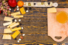 Variety of Cheeses and Fruit on Wooden Table Stock Photo