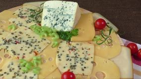 Variety of cheeses on a wooden board stock video footage
