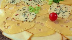 Variety of cheeses. On a wooden board stock footage