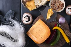 Variety of cheeses on a wooden board. Mushrooms, spices, peppers. Dark photo. Ingredients. stock image