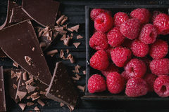 Variety of chopping chocolate with raspberries. Dark and milk chopping chocolate and chips with fresh raspberries in black wood box over black burnt wooden Royalty Free Stock Photos