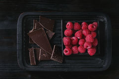 Variety of chopping chocolate with raspberries. Dark and milk chopping chocolate and chips on old plate with fresh raspberries in black wood box over black burnt Royalty Free Stock Photo