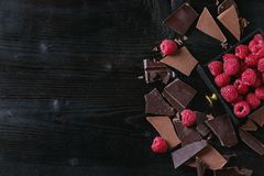 Variety of chopping chocolate with raspberries. Dark and milk chopping chocolate and chips shavings chopping chocolate with fresh raspberries in black wood box Stock Images